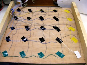 The bottom of the game board. Reed switches attached with coloured electrical tape to make logical layout.
